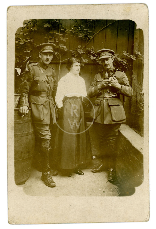 Harry Colebourn standing with woman and a solider holding small dog